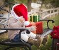 Skämtsamt barn som bär santa hat sitting med julgåvor utanför Arkivfoto
