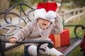 Skämtsamt behandla som ett barn bärande santa hat sitting med julgåvor utanför Arkivfoton