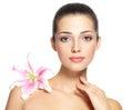 Skönhetframsida av den unga kvinnan med blomman skönhetbehandlingbegrepp Royaltyfri Foto