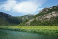 Skadar lake national park in montenegro green mountain shore on a sunny day Stock Photos