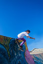 Skateboarder down ramp park teenage grinds the with blue sky at durban beachfront bike skateboard Stock Images