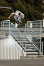 Skateboarder jumping over handrail Stock Image