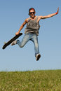 Skateboarder leaping in the air agile casual young male high on his skateboard over green grass against a clear sunny blue sky Stock Photos