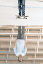 Skateboarder riding a skateboard on the street or park freestyle with reflection after rain Stock Image