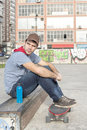 Skateboarder sitting in the park with skate and bottle of energy Royalty Free Stock Image