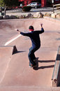Skateboarder in skate park practicing skateboarding tricks a Royalty Free Stock Photos