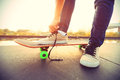 Skateboarder tying shoelace on city vintage effect Royalty Free Stock Image