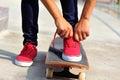 Skateboarder tying shoelace at skate park morning Royalty Free Stock Photo