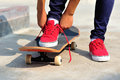 Skateboarder tying shoelace at skate park morning Royalty Free Stock Photo