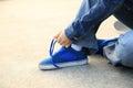Skateboarder tying shoelace at skate park morning Royalty Free Stock Image