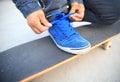 Skateboarder tying shoelace at skate park morning Royalty Free Stock Photography