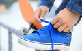 Skateboarder tying shoelace at skate park morning Royalty Free Stock Photography