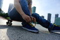 Skateboarder tying shoelace at skate park Royalty Free Stock Photo