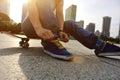Skateboarder tying shoelace at skate park morning Royalty Free Stock Photos