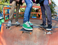 Skateboarders three friends in the halfpipe skatepark Royalty Free Stock Photo