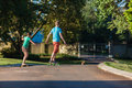 Skateboarding boy girl and down the tarred asphalt road driveway late afternoon light Royalty Free Stock Photo