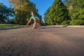 Skateboarding girl fun young having on the tarred asphalt road driveway late afternoon light Stock Photo