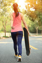 Skateboarding woman asian walking with skateboard Stock Photo
