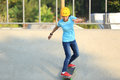 Skateboarding young woman riding on a skateboard at skatepark Stock Photo