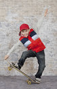 Skater boy crouching his skateboard front brick wall Royalty Free Stock Photo