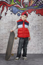Skater boy in front of wall with his skateboard brick covered with graffiti Royalty Free Stock Photo