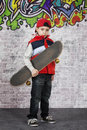 Skater boy with his skateboard in front of wall covered graffiti Stock Photography