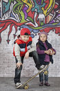Skater boy with a little girl and in front of the wall covered graffiti Stock Image