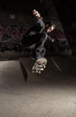 Skater doing huge ollie in the skate park with ramp behind him Royalty Free Stock Photo