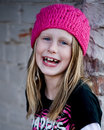 Skater girl in pink hat laughing beautiful little next to white wall wearing knit and joyfully Stock Images