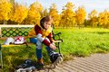 Skater putting on rollers nice years old boy in casual autumn clothes roller skates sitting the bench in the park Royalty Free Stock Photos