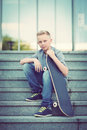 Skaterboy young boy with his skateboard sitting on the stairs Royalty Free Stock Images
