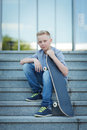 Skaterboy young boy with his skateboard sitting on the stairs Stock Images
