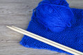 Skein of blue yarn with completed knitting and bamboo needles Stock Images