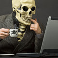 Skeleton drinks poisonous coffee with laptop Stock Photo