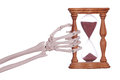 Skeleton hand holding sand timer on white Stock Image