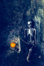 Skeleton with jack o lantern sitting in forgotten grave Stock Photos