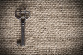 Skeleton key an old metal sitting on a piece of brown burlap horizonal format and vignetted edges for a vintage effect Stock Image