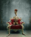 Skeleton king on baroque chair Royalty Free Stock Photos