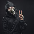 Skeleton showing two fingers scary in a robe Royalty Free Stock Photos