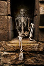 Skeleton sitting in an alcove of ruined abbey Stock Image