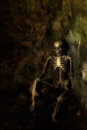 Skeleton sitting in the corner of forgotten grave at halloween Stock Photography