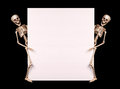 Skeletons holding empty blank over black halloween background Royalty Free Stock Photography