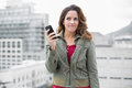 Skeptic gorgeous brunette in winter fashion holding smartphone on urban background Royalty Free Stock Photos