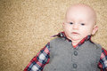 Skeptical baby wearing gray vest a with a big smile blue eyes a and red white and blue plaid shirt and a serious expression on his Royalty Free Stock Images