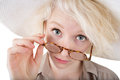 Skeptical blond female looking over eyeglasses on isolated background Royalty Free Stock Photo
