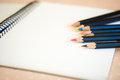 Sketch pad with colored pencils a white papered spiral bound a selection of on a page Stock Photo