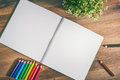 Sketch pad and colored pencils on a wooden table Stock Image