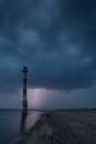 Skew lighthouse in the Baltic Sea. Stormy night and lightning. Royalty Free Stock Photo