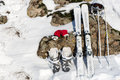 Ski equipment leaning on rocks and snow winter sports setup displaying red gloves pair of skis boots helmet poles surface of stone Stock Images