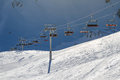Ski lift carrying skiers, snowboarders on a bright sunny winter day